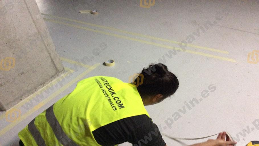 Quitar cinta después de pintar el suelo en la señalización en un pavimento industrial