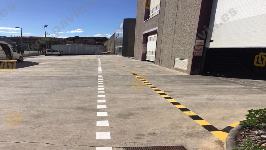 Señalización industrial de la línea amarilla y negra en zona exterior para el paso de puertas