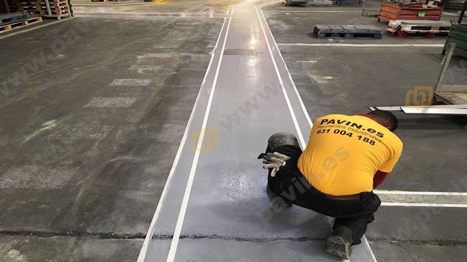 colocación de la cinta en el pavimento de hormigón para la señalización industrial para automoción