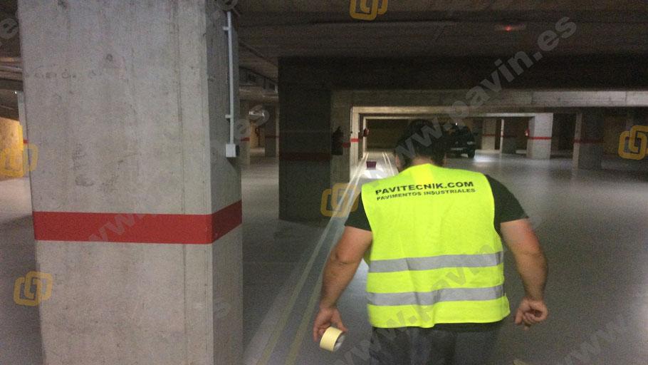 Colocación de la cinta para marcar la señalización en un pavimento industrial