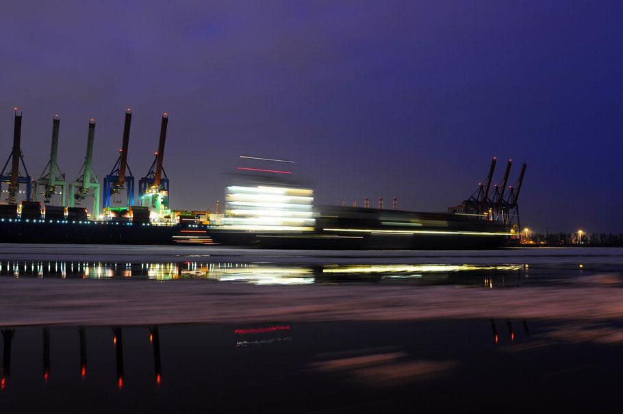 Blick vom Museumshafen Övelgoenne auf den HHLA Container Termial und einem fahrenden Schiff im Winter mit Eisgang bei Nacht.