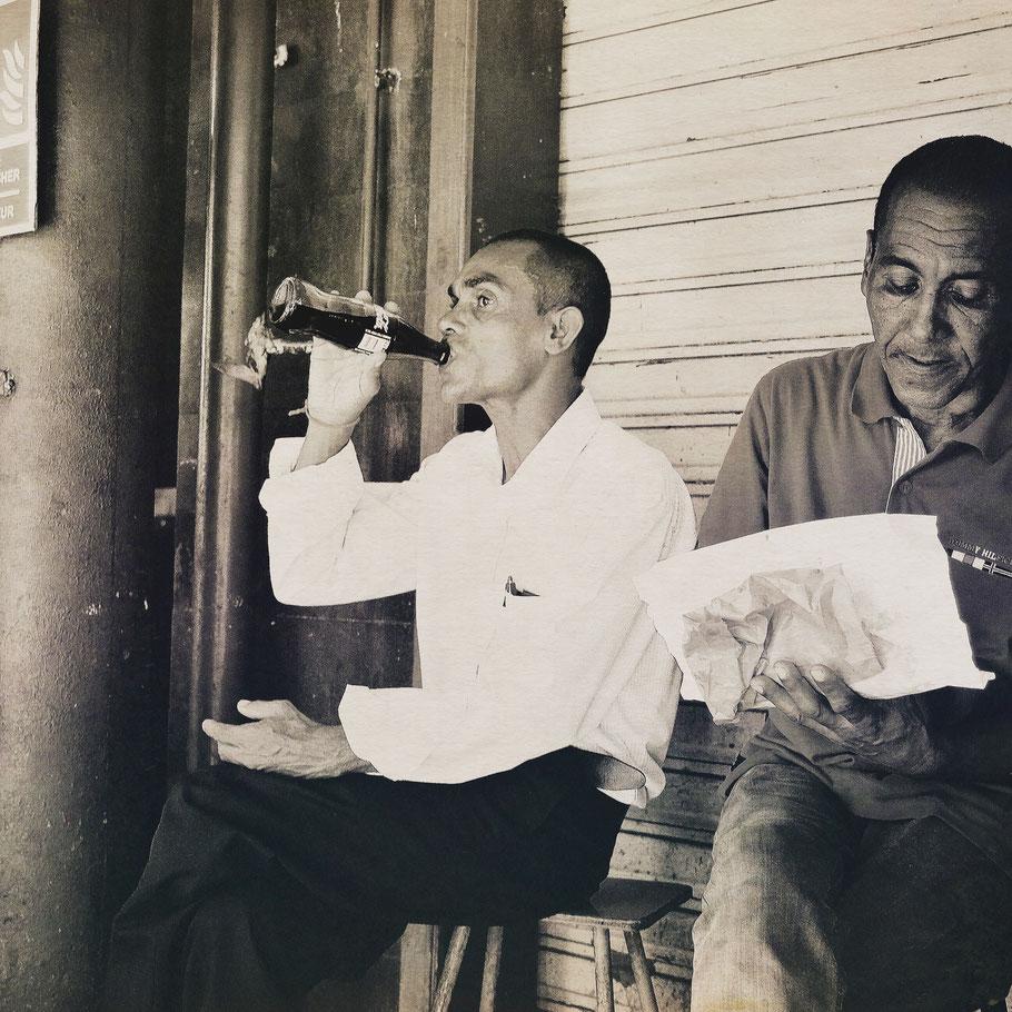 Mauritius market, man drinking coke