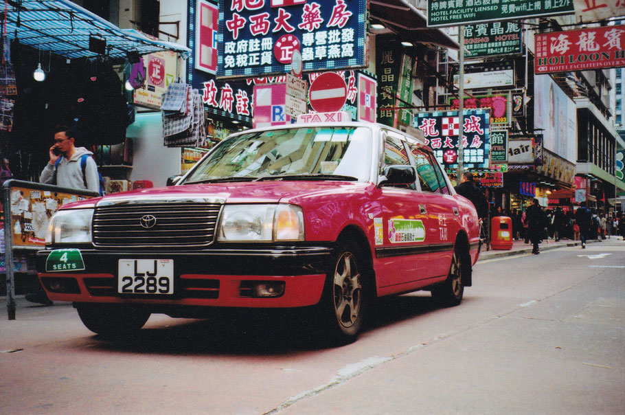 The iconic pink taxis and the stacked up businesses and street signs. Imagine it's 32 degrees celsius and you smell cooking oil and pollution. You're in HK