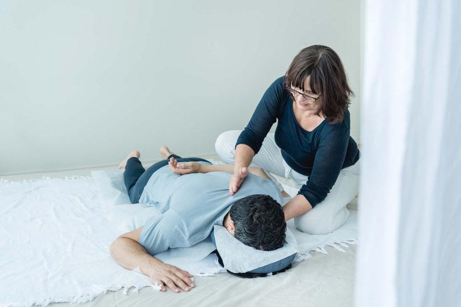 Shiatsubehandlung Rücken, Mann auf Bauch am Boden liegend