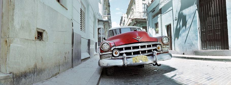 Roter Oldtimer ohne Vorderrad steht auf der Straße in der Altstadt von Havanna als Farbphoto im Panoramaformat, Cuba