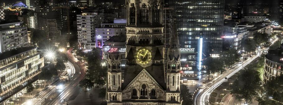 Nachtaufnahme mit Spiegelungen Kaiser-Wilhelm-Gedächtnis Kirche  in Berlin als Farbfotografie im Panorama-Format