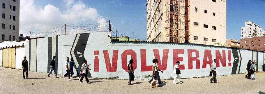 """Kubaner gehen vor einer Wand mit der Aufschrift """" Volveran!"""" Havanna zur Arbeit, Farbphoto als Panorama-Photographie"""