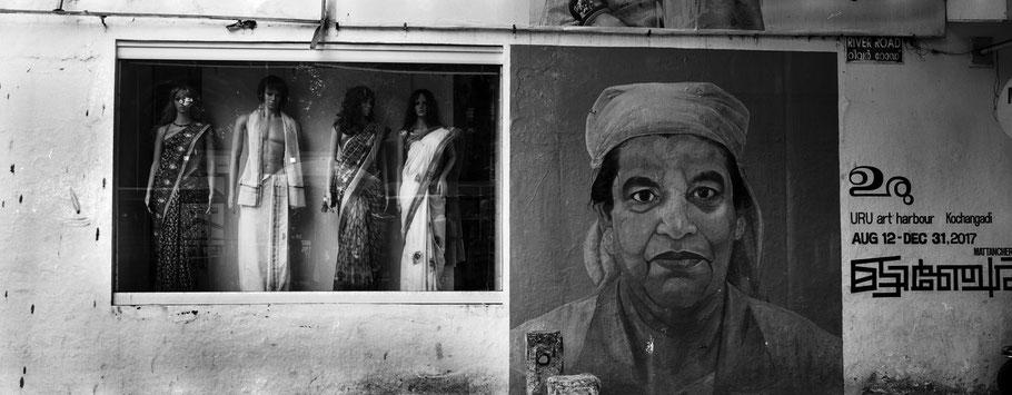 Schaufenster und Werbung in der Dämmerung in Kochin, Indien, in schwarz-weiß als Panorama-Photographie