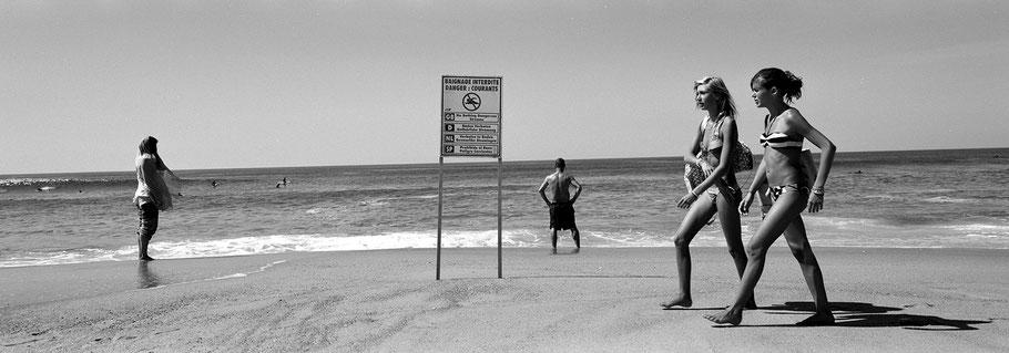 Zwei junge Mädchen spazieren auf dem Strand von Moilet et Mare in schwarzweiß als Panorama-Photographie