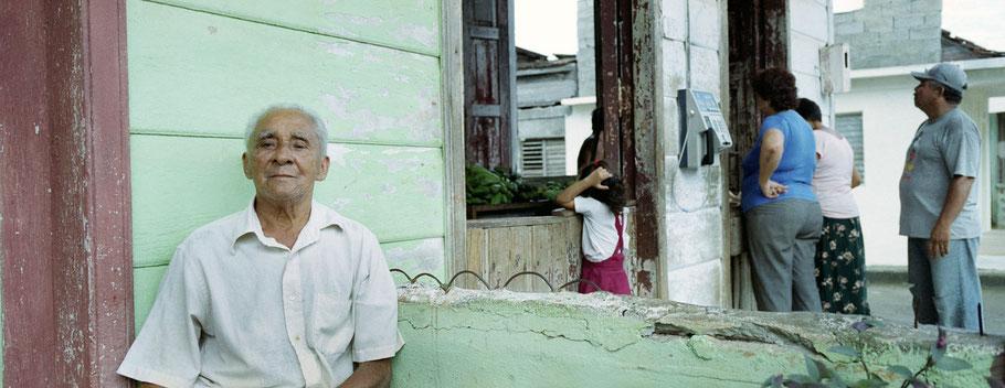 Alter Cubaner sitzt vor einem Laden in Baracoa als Panorama-Photographie