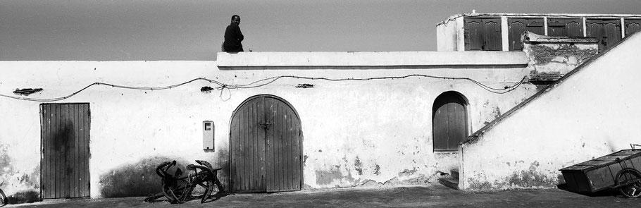 Fischer im Hafen von Essaouira in Marokko in schwarz-weiß als Panorama-Photographie