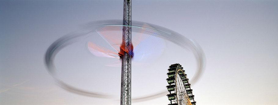 Nächtliche Aufnahme der Fahrgeschäfte auf dem Oktoberfest in München als Farbphoto im Panorama-Format