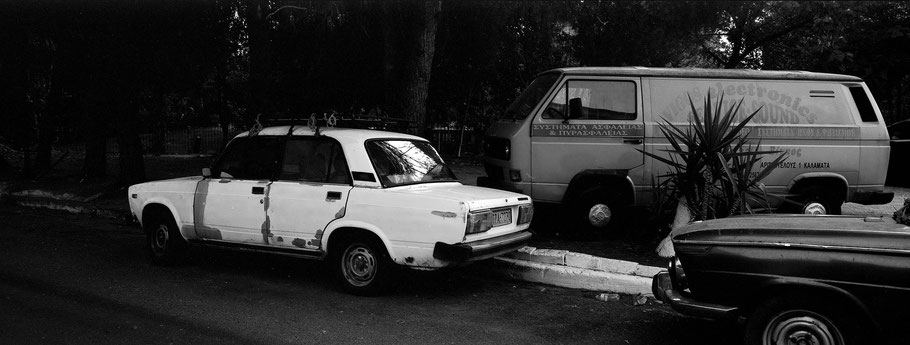 Alter Lada, BMW und VW T2 in Kalamata auf dem Peloponnes, Griechenland,  als Schwarzweißphoto im Panorama-Format