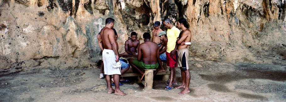Acht Kubaner spielen in Maguana ein Brettspiel in der Natur, Farbphoto als Panorama-Photographie