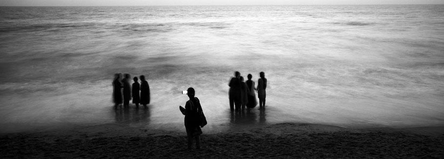 Lehrer fotografiert mit Mobiltelefon in der Dämmerung Schülerinnen am Strand in schwarz-weiß als Panorama-Photographie