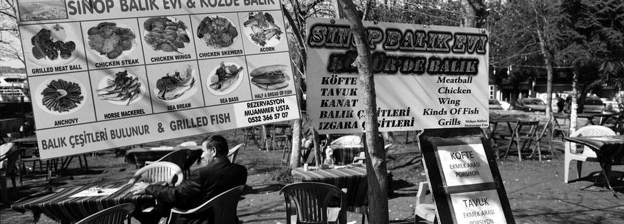 Mann auf dem Fischmarkt  in Karaköy in Istanbul, Türkei als Schwarzweißphoto im Panorama-Format