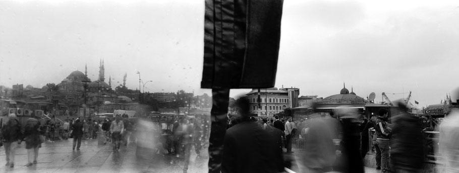 An der der Galata Brücke im Regen in Istanbul, Türkei als Schwarzweißphoto im Panorama-Format