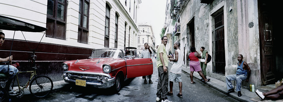 Roter Oldtimer in der Altstadt von Havanna als Farbphoto im Panoramaformat, Cuba