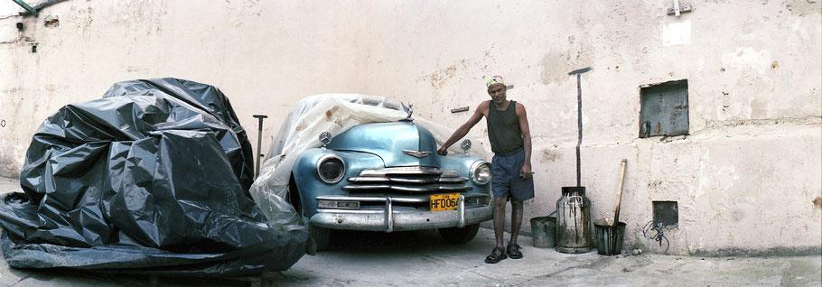 Kubaner posiert vor alten Autos im Hof in Havanna, Farbphoto als Panorama-Photographie