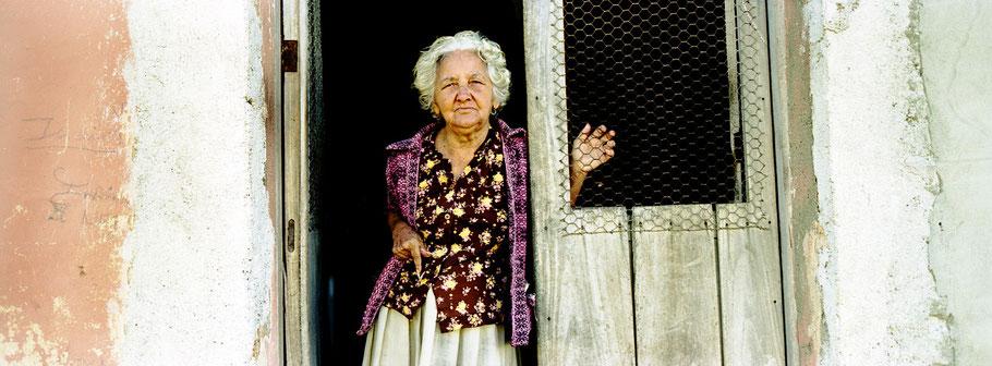 Alte kubanische Frau schaut in Trinidad d. Cuba aus der Haustür heraus, Farbphoto als Panorama-Photographie