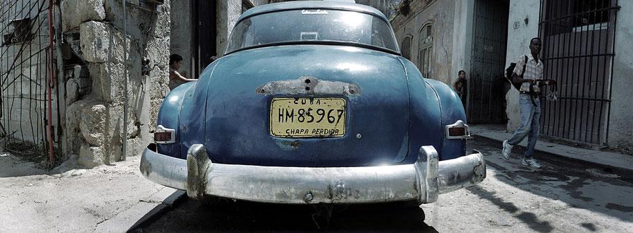 Blauer Oldtimer steht auf der Straße in der Altstadt von Havanna als Farbphoto im Panoramaformat, Cuba