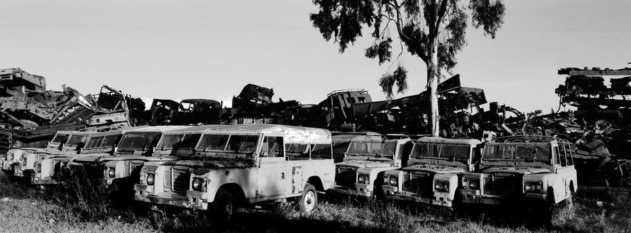 Kriegsschrott aufgetürmt im Tank Graveyard in Asmara, Eritrea, als Schwarzweißphoto im Panorama-Format