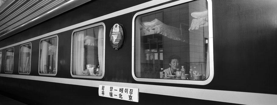 Frau schaut aus dem Abteil im Zug von Peking nach Pyongyang, Nord Korea, in schwarz-weiß als Panorama-Photographie