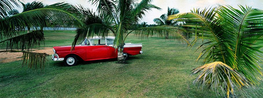 Roter Oldtimer auf der Wiese in Varadero als Farbphoto im Panoramaformat, Cuba