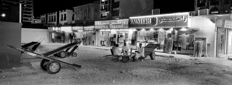 Vier Männer sitzen auf Sackkarren im Souk in Dubai als Panorama-Photographie