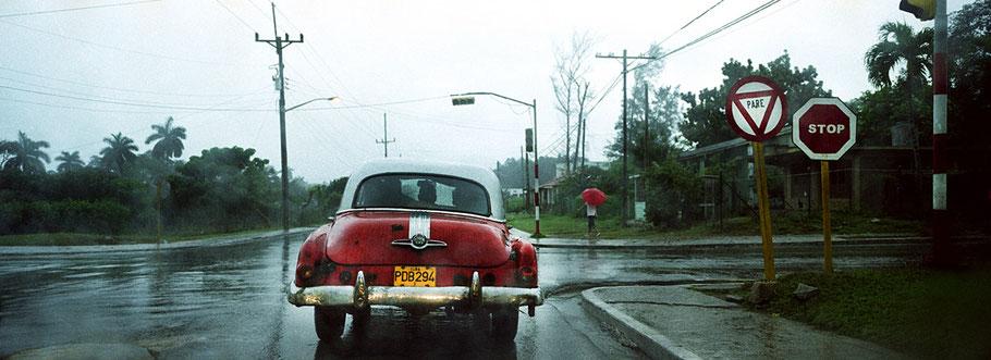 Roter Oldtimer steht im Regen am Stoppschild in Pinar del Rio als Farbphoto im Panoramaformat, Cuba