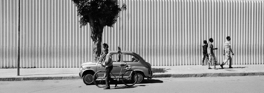 Junge Männer in der Mai Bela Avenue in Asmara, Eritrea, als Schwarzweißphoto im Panorama-Format