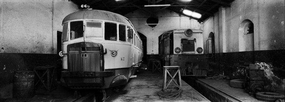 Zwei alte Triebwagen in der Werkstatthalle der Asmara Ferrovia als Schwarzweißphoto im Panorama-Format