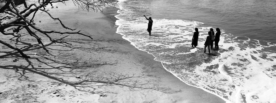 Schülerinnen machen am Strand von Fort Kochin, Indien, ein Selfi in schwarz-weiß als Panorama-Photographie