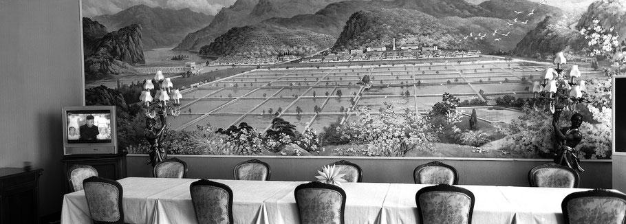 Leeres Restaurant in Sariwon mit Fernseher und Wandgemälde, Nord Korea,  in schwarz-weiß als Panorama-Photographie