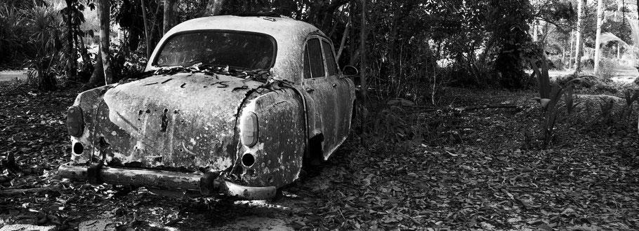 Reste von Oldtimer-Taxi bei Marari in Kerala , Indien, als Schwarzweißphoto im Panorama-Format