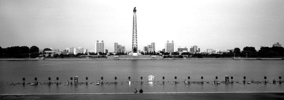 Blick über den Taedong River  auf den Juche Turm in Pyongyang, Nord Korea, als Schwarzweißphoto im Panorama-Format