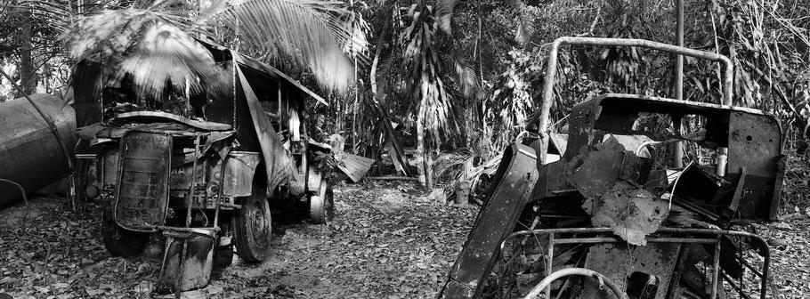 Reste von Oldtimern bei Marari in Kerala , Indien, als Schwarzweißphoto im Panorama-Format