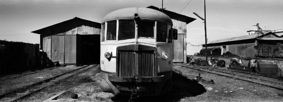 Fiat Triebwagen vor der Werkstatthalle der Asmara Ferrovia als Schwarzweißphoto im Panorama-Format