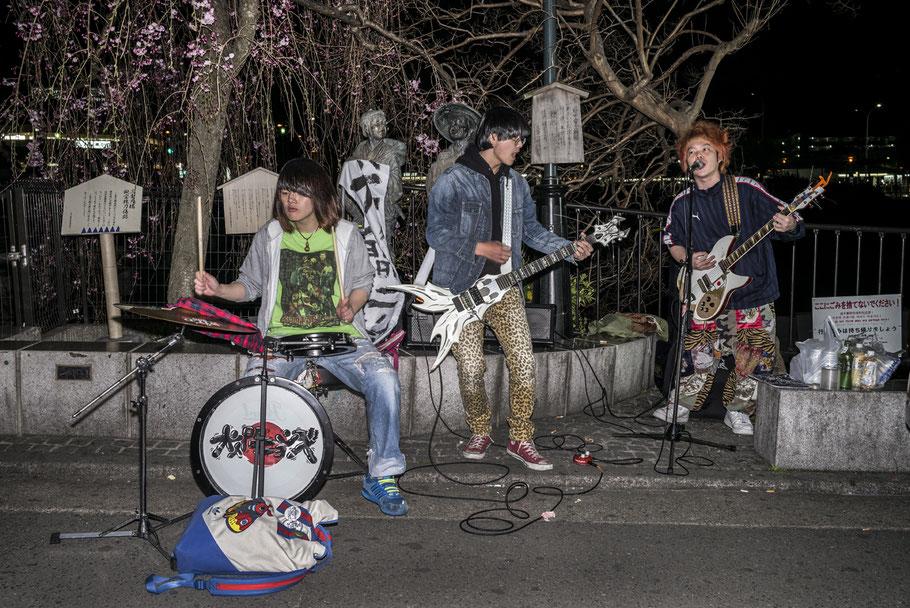 Eine Band als Straßenmusiker in Kyoto abends als Farb-Photographie, Japan