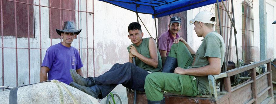 Vier junge  Kubaner posieren an der Straße in Remedios, Farbphoto als Panorama-Photographie