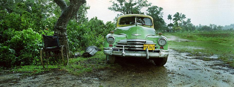 Grüner Oldtimer steht im Regen nähe San Juan Y Martinez als Farbphoto im Panoramaformat, Cuba