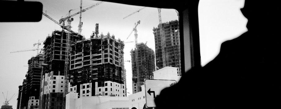 Blick aus dem Minibus auf die Häuserfassaden im Rohbau in der Al Sutouth Road, Dubai, als Panorama-Photographie