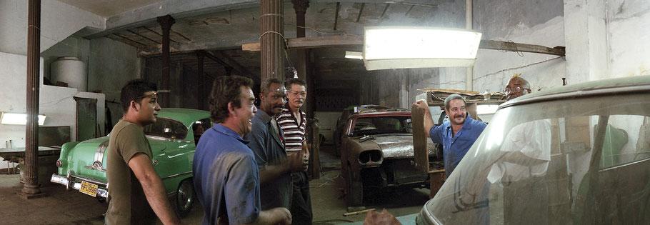 Kubanische KFZ-Mechaniker posieren vor alten Autos in einer Werkstatt in Havanna, Farbphoto als Panorama-Photographie