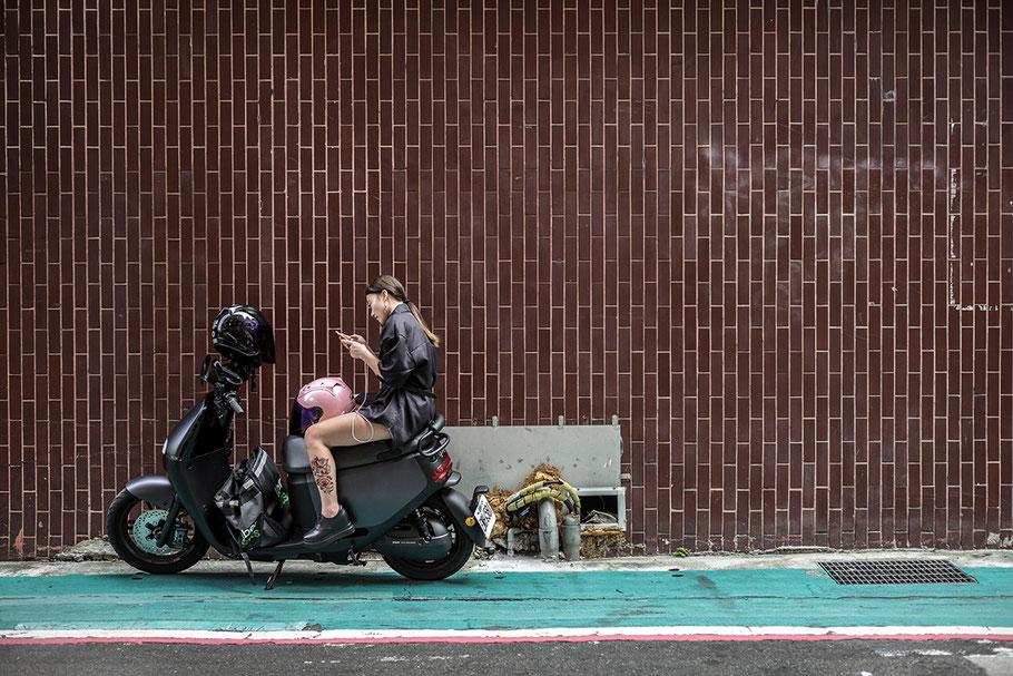 Junge Taiwanerin auf Motorrad in der  Xinyi Road in der Nähe des Taipei 101 im Zentrum von Taipei, Taiwan, als Farbphoto