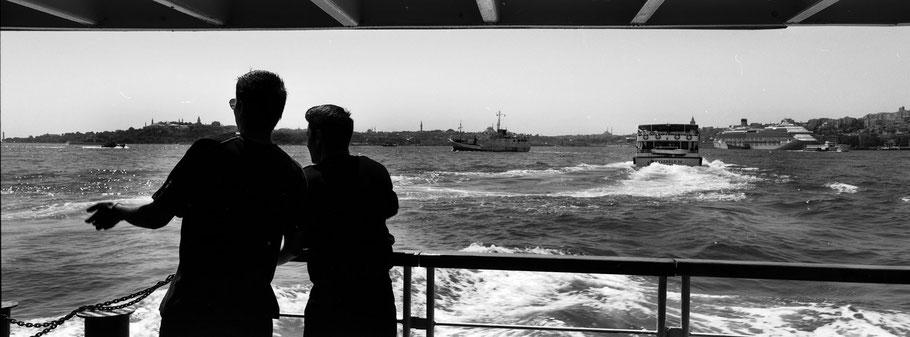 Auf der Fähre mit Blick über den Bosporus in Istanbul, Türkei als Schwarzweißphoto im Panorama-Format