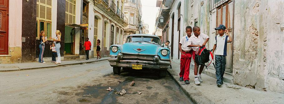 Straßenszene in der Calle San Ignacio mit Oldtimer und Kindern in Havanna, Cuba, als Farbphoto im Panorama-Format