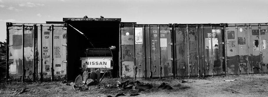 Container mit Toyota im Tank Graveyard in Asmara, Eritrea, als Schwarzweißphoto im Panorama-Format