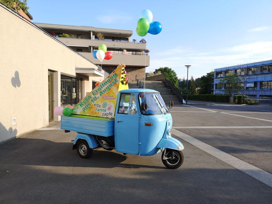 Nostalgisch 50-er Jahr blaues Piaggo-3-Rad mit Anhänger auf dem Dorfplatz von Langnau. Auf dem Anhänger als 3-eckiges Skulptur Werbung zur Kita-Eröffnung am 10. August.