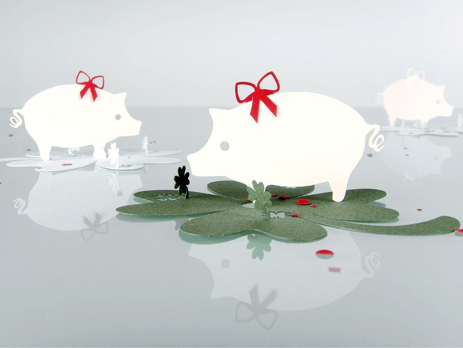 filigrane Papierarbeiten: kleine Glücksschweinchen aus Caslon-Papier geschnitten mit roter Glückwunschschleife und einem grünen Kleeblatt