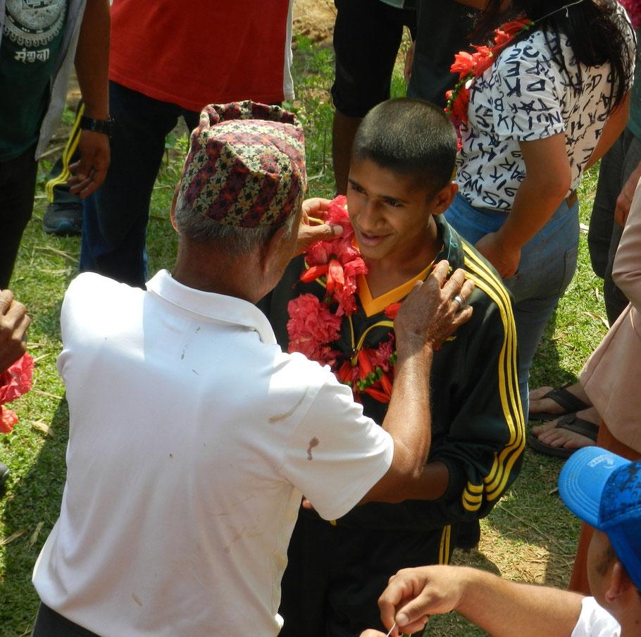 Ein glücklicher Dorfbewohner und ein glücklicher Helfer: Sanjeev bekommt als Ausdruck der Begrüßung und Dankbarkeit eine Blumenkette überreicht.